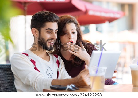 Shocked young couple watching something on the digital tablet while sitting in the cafe - stock photo