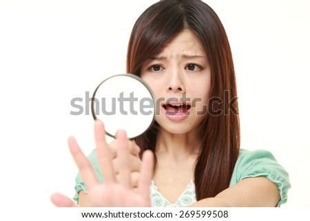 shocked young Japanese woman looking through a magnifying glass her nails - stock photo