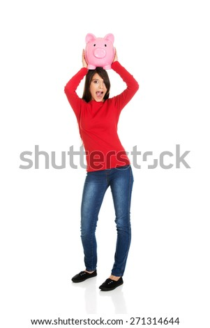 Shocked young student woman with piggybank. - stock photo