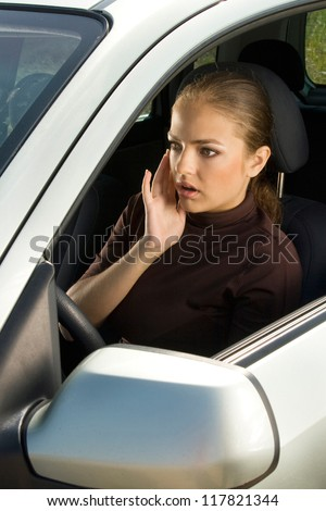 Shocked young woman driver sits in the car and looks ahead.