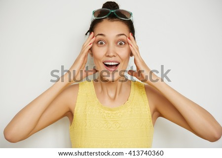 Shocked young woman looking surprised at the camera, holding her head in excitement. Close up view of beautiful female with brown eyes and bun hairstyle posing indoor against white studio background   - stock photo