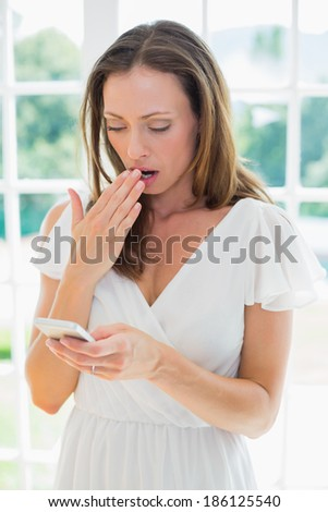 Shocked young woman reading text message at home - stock photo