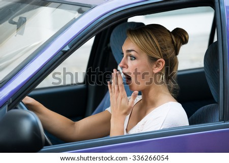 Shocked young woman with mouth open driving car - stock photo