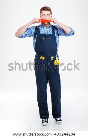 Shocked young worker in overall with mouth covered by red adhesive tape - stock photo
