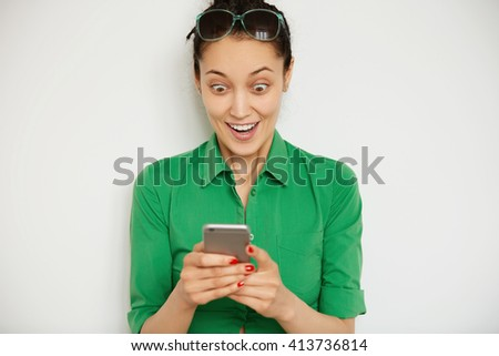 Shocking news! Business and technology. Close up portrait of surprised young woman in casual clothes reading sensational news on smart phonewith astonished expression . Isolated against white wall - stock photo