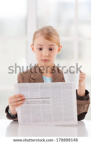 Shocking news. Surprised little girl in formalwear reading newspaper and holding a cup while sitting at the table