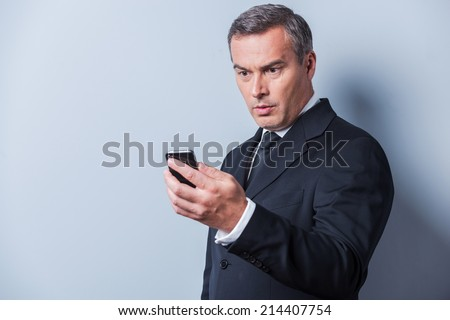 Shocking news. Surprised mature man in formalwear holding mobile phone and looking at it while standing against grey background