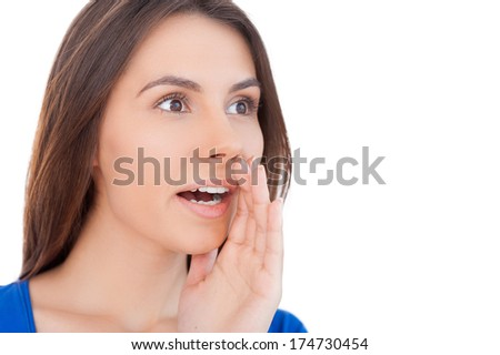 Shocking news! Surprised young woman shouting and holding hand near mouth while isolated on white - stock photo