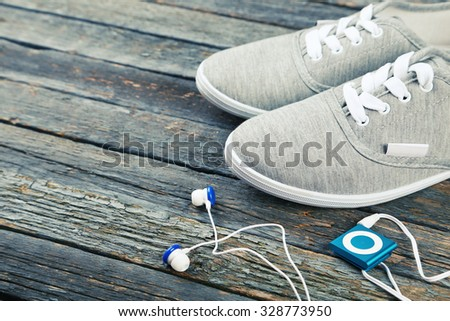 Shoe and headphones on blue wooden background