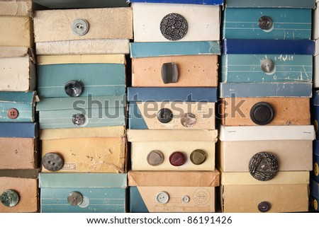Shoe boxes piled up containing a categorized collection of cloth buttons