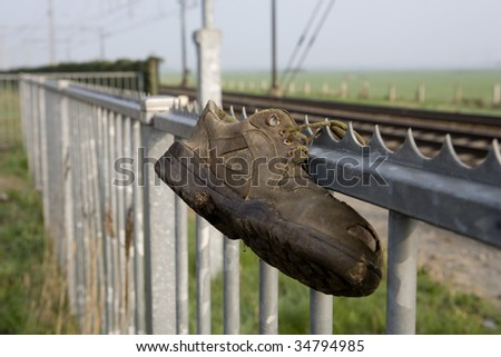 Shoe hanging on a fence