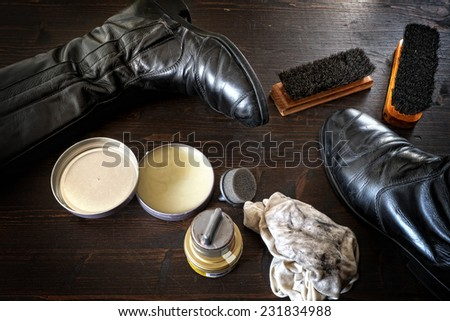 Shoe polish. Shoes and polishing equipment on dark brown wooden surface - stock photo