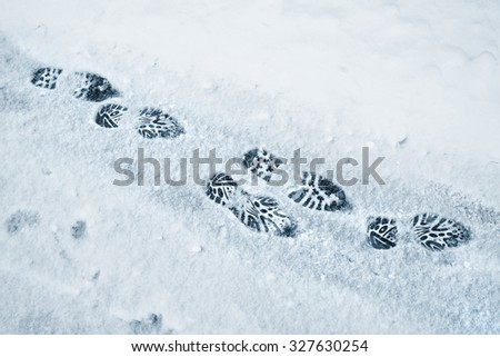 Shoe prints in the fresh snow on the asphalt street.  - stock photo