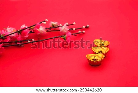 Shoe-shaped gold ingot (Yuan Bao) and Plum Flowers on red background - best for Chinese New Year use - stock photo