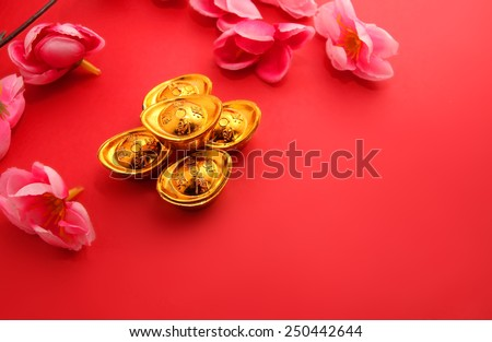 """Shoe-shaped gold ingot (Yuan Bao) (with the words """"zhao cai jin bao"""" meaning money come in) and Plum Flowers on red background with copy space - best for Chinese New Year use - stock photo"""