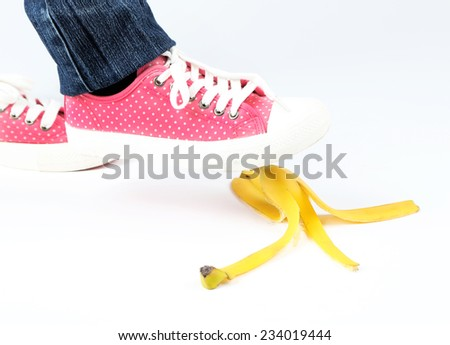 Shoe to slip on banana peel and have an accident, isolated on white - stock photo