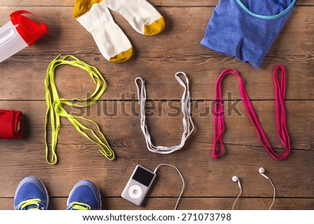 Shoelaces run sign and various running stuff on a wooden floor background - stock photo