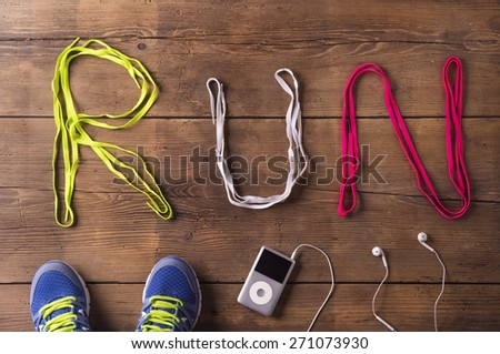 Shoelaces run sign, running shooes and mp3 player on a wooden floor background - stock photo