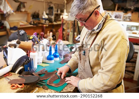 Shoemaker cutting and gluing leather in a workshop