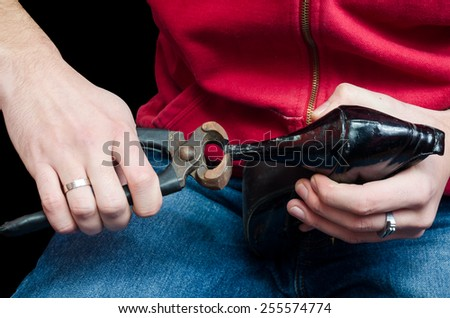Shoemaker repairing a old pair of shoes with a tool - stock photo