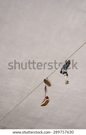 shoes and a can hanging on a rope - stock photo