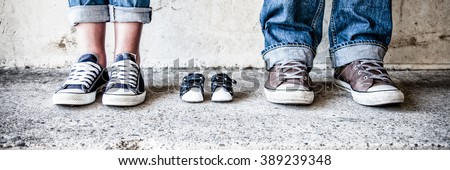 shoes and sneakers of parents and expected baby - stock photo