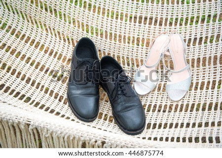 Shoes for men and women in a hammock in the wedding ceremony. - stock photo