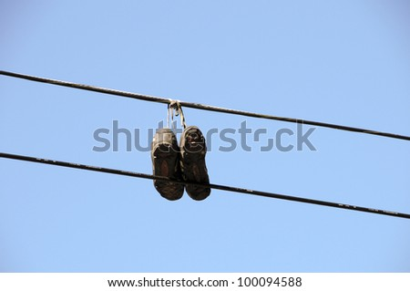 Shoes hanging from a cable - stock photo