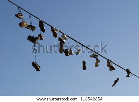 Shoes hanging on a cable - stock photo