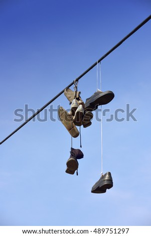 Shoes hanging on a string against blue sky