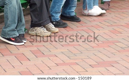 Shoes lined up on brick walkway - stock photo