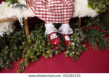 Shoes of a happy, laughing girl, child in a Christmas dress, sitting on a sled with christmas trees and ornaments on red background. X-mas happiness concept. - stock photo