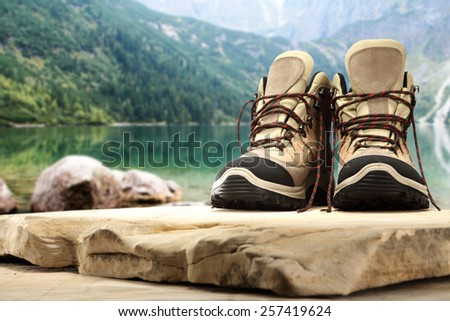 shoes of brown color and stone top on coast of lake  - stock photo