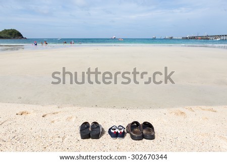 Shoes of family on the beach. - stock photo