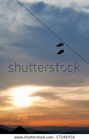 Shoes on hanging on a power line - stock photo