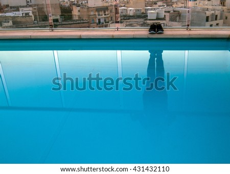 shoes on side but lady reflection in pool on rooftop in city