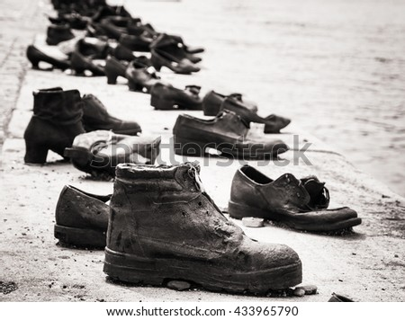 Shoes on the Danube bank is a memorial in Budapest, Hungary. Place of reverence. Black and white photo. Cultural heritage. Symbolic object. Shoes monument. - stock photo