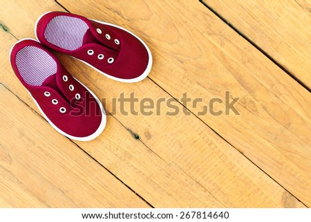 Shoes on wooden background. Red sneakers - stock photo