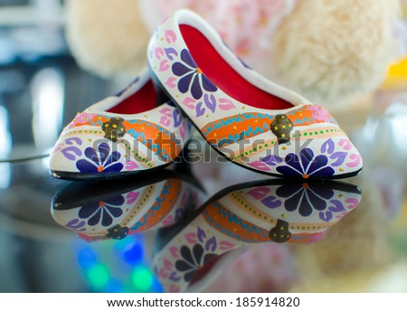 shoes with floral ornament on glass and reflection. - stock photo