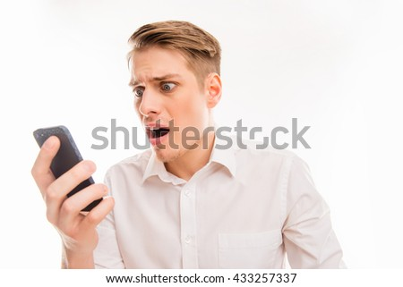 Shoked young man holding phone and reading message