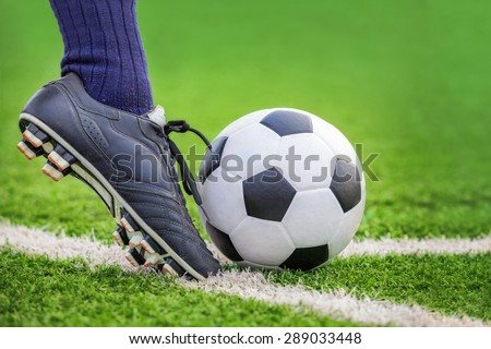 Shoot a soccer ball with his feet on the football field - stock photo