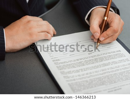 Shoot of financial director's hands signing business contract at the desk in his office.