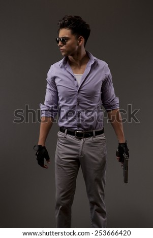 shooter or contractor looking right on grey background with gun - stock photo