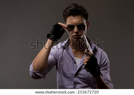 shooter or contractor with gun attempting to remove his glasses - stock photo