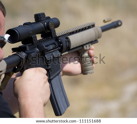 Shooter who has just taken a shot with an assault rifle - stock photo
