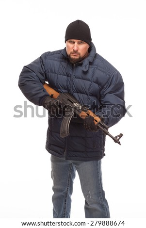 Shooter with AK 47 and cold weather looking at camera on white background. - stock photo
