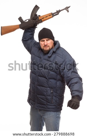 Shooter with AK 47 looking forward with cold weather gear ready to fight with rifle up in air on white background. - stock photo