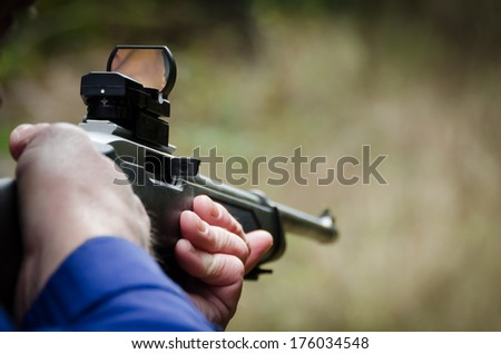 Shooting a rifle and a red dot site in Oregon. - stock photo