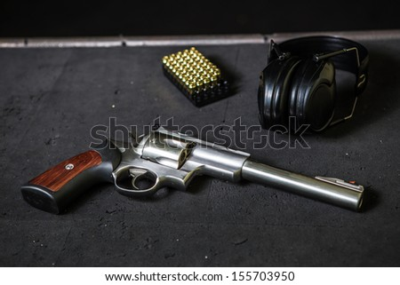 shooting bullets with gun and headphones - stock photo