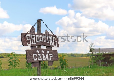 Shooting camp wooden sign on sky and grass field  background